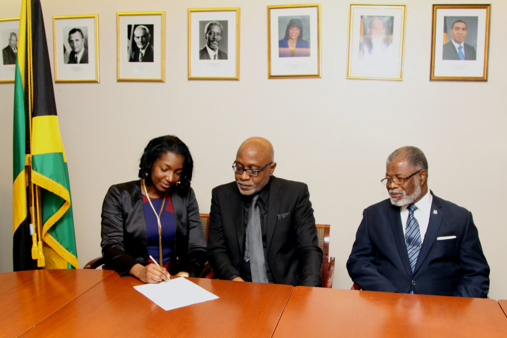 Niambe McIntosh signing the Peter Tosh museum agreement.